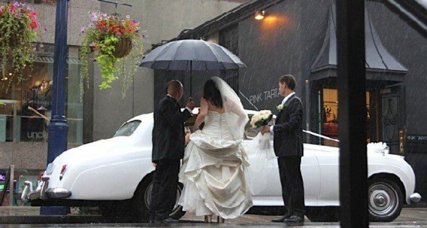 Bride Entering Vintage Bentley in Rain
