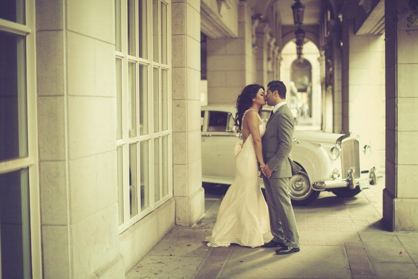 Wedding Couple kissing in front of our Vintage Bentley Car